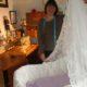 Ann sy ett draperi för spädbarnssängen i semesterlägenheten